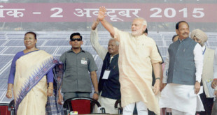Khunti : Prime Minister Narendra Modi waves at crowd Governor of Jharkhand Draupadi Murmu and Chief Minister Raghubar Das look on during inauguration of Rooftop Solar Power Plant at District Court in Khunti on Friday. PTI Photo  (PTI10_2_2015_000094B)