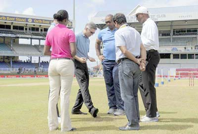 Umpire Nigel Llong (2L) illustrates a point to Phil Simmons (3L) Head Coach of West Indies and other match officials while inspecting the field during day 4 of the 4th and final Test between West Indies and India August 21, 2016 at Queen's Park Oval in Port of Spain, Trinidad. / AFP PHOTO / Randy BROOKS