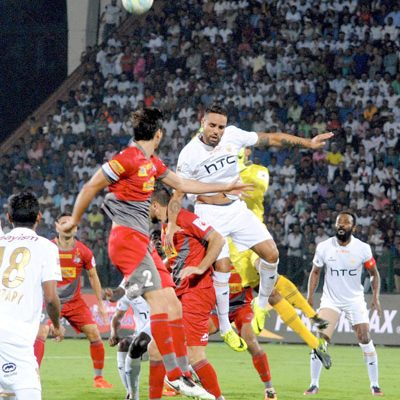 Players of Northeast United FC (in white jersey) and Atletico de Kolkata (in red  jersey) vie for the ball during the ISL match at Indira Gandhi Athletics Stadium, in Guwahati on Friday.