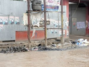A power conduit stands amid a half-closed but overflowing culvert along Kalibari Road in Dimapur.